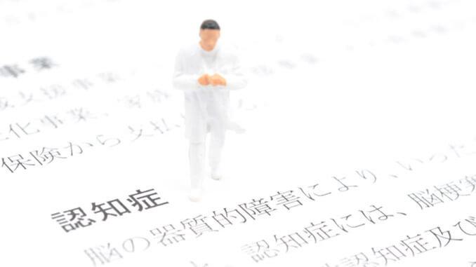 「認知症」という文字の上に立つ医療従事者の人形.jpg