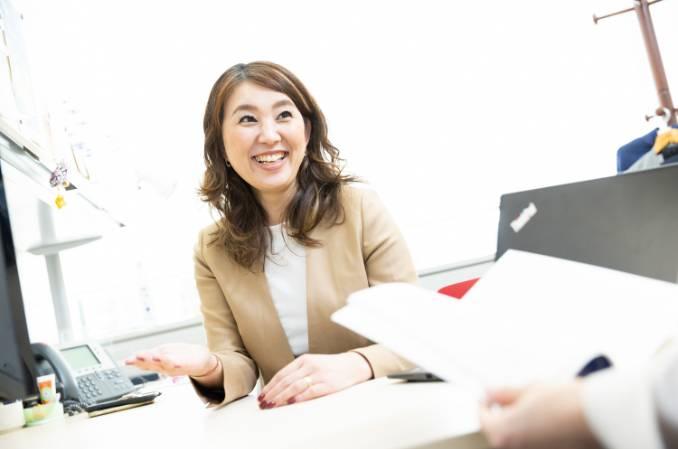 机を挟んで同僚と談笑する若い女性